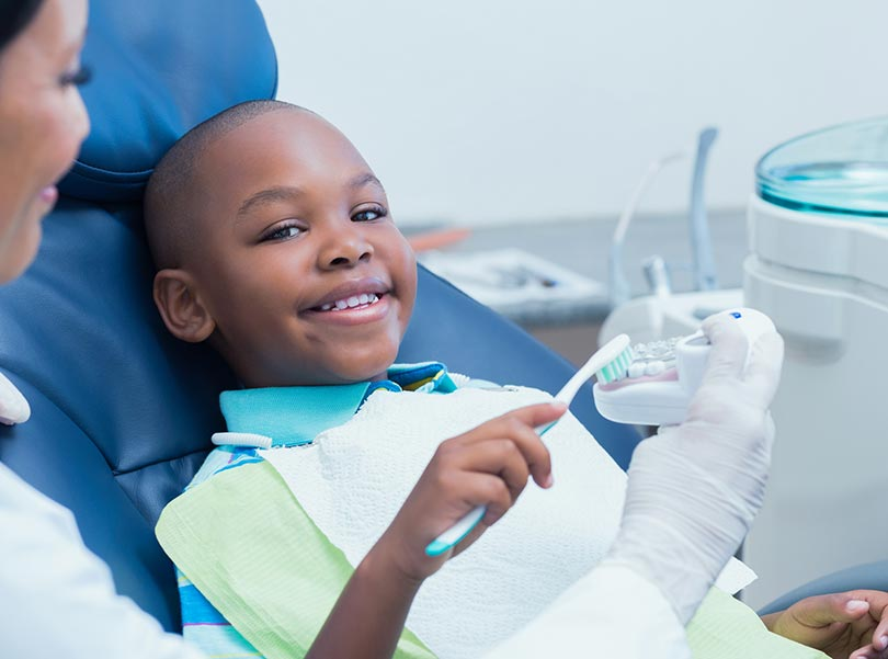 Dentist is teaching dental cleaning to a boy