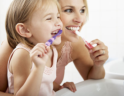 Mom and kid are brushing their teeth